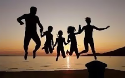 Family on the beach jumping for joy in the sunset